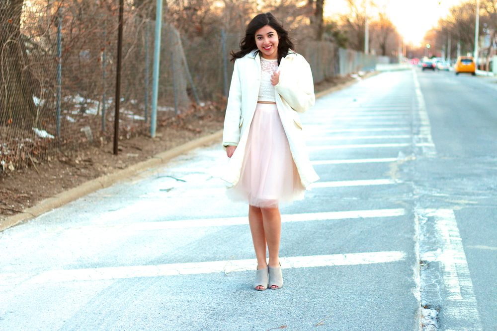 For this outfit I wore a tulle skirt, lace top, and gray booties, but added a white knee length coat for a polished look.  I recommend adding a light-colored handbag which will look great with the white, pink, and gray tones of this outfit.
